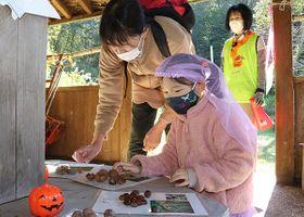 木の実を触ってクイズに答える親子連れ=県自然博物園ねいの里