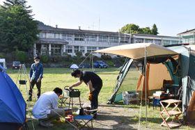 校舎が見える校庭でキャンプを楽しむ利用客ら=南足柄市内山