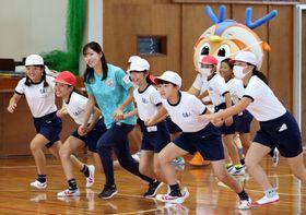 子どもたちと楽しく体を動かす新任普及インストラクターの小柳さん(左から3人目)=有喜小体育館