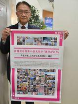台湾から届いたポスターを手にする旦野隆晃会長=美濃市松森、サピーショッピングセンター