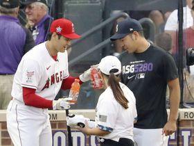 本塁打競争1回戦の合間に、マリナーズ・菊池(右)から飲み物を受け取るエンゼルス・大谷=7月12日、デンバー(共同)