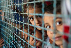 18日、パレスチナ自治区ガザで、イスラエル側の攻撃から逃れるため、自宅から国連が運営する学校に避難した子どもたち(ロイター=共同)