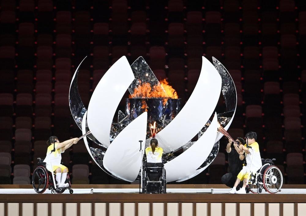 2021年8月24日撮影、オ電479Sの字句を差し替え  東京パラリンピックの開会式で、聖火台に点火する(左から)パワーリフティング女子の森崎可林、車いすテニス女子の上地結衣、ボッチャの内田峻介=24日夜、国立競技場