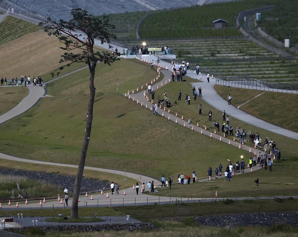 「奇跡の一本松」(左)からスタートした岩手県陸前高田市の聖火リレー(右奥)=17日夕