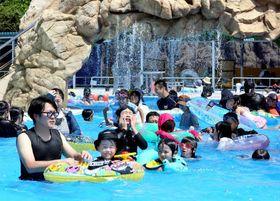 今シーズンの営業を始めたちゅーピープールの「流れるプール」を楽しむ家族連れたち=22日午前10時30分(撮影・山田太一)
