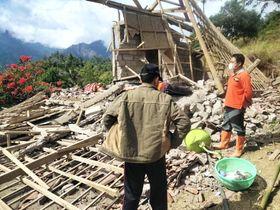 インドネシア・バリ島で、地震で倒壊した建物付近を調べる災害救助当局者ら=16日(国家災害対策庁提供・共同)