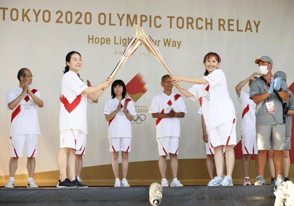 1980年モスクワ五輪で「幻の代表」となったメンバーの赤羽綾子さん(手前右)に聖火を引き継ぐ笹田夏実さん=22日午後、東京都港区(代表撮影)