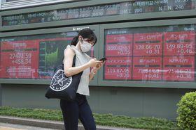 株価ボードの前を歩く女性=8月、東京(AP=共同)