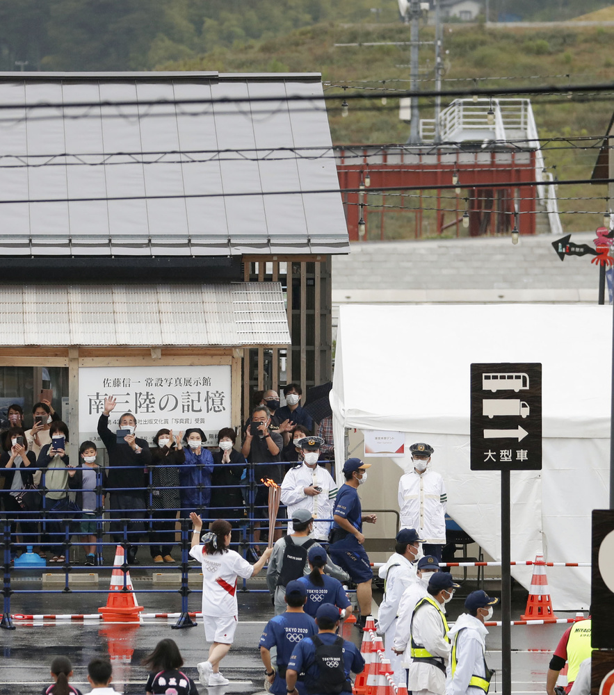 宮城県南三陸町の「南三陸さんさん商店街」で行われた聖火リレー。右上は東日本大震災で町職員ら43人が犠牲になった旧防災対策庁舎=19日午後