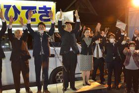 桜川市長選で3回目の当確が確実となり、万歳する大塚秀喜氏(中央)ら=17日午後8時42分ごろ、桜川市真壁町古城