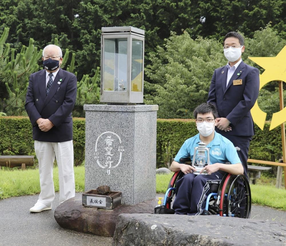 「3・11希望の灯り」から採火された、東京パラリンピック聖火が入ったランタンを手に記念撮影に応じる高橋未宇さん(右手前)と藤原直美さん(左)=12日午前、岩手県陸前高田市