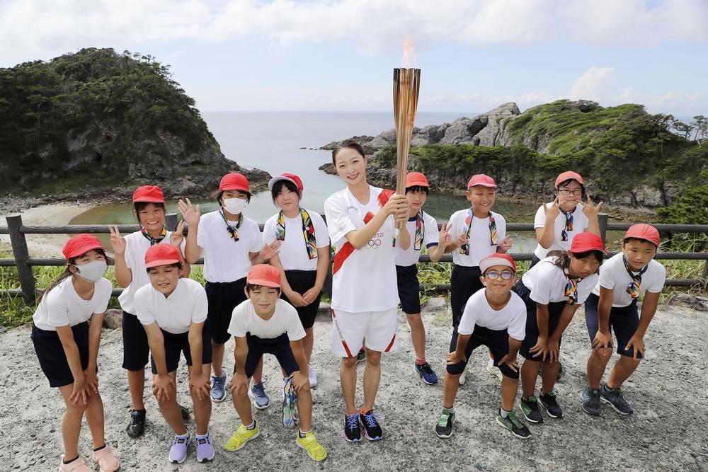 東京都の式根島で行われた聖火リレーで、トーチを掲げて子どもたちと記念撮影する新体操団体でロンドン、リオ五輪に出場の畠山愛理さん=15日午後(代表撮影)