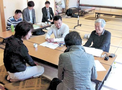 只越地区の住民に住宅再建の意向を聞く野崎さん(右)=2012年5月、気仙沼市(野崎さん提供)
