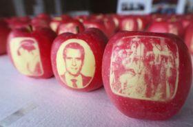フランスのマクロン大統領の顔(手前中央)などが浮き上がった「絵入りリンゴ」=26日午前、青森県弘前市