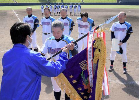 表原市長(左)から優勝旗を受け取る徳島GOクラブの代表