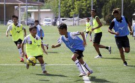 8対8のゲームで交流を深めた愛媛FCトップチームとFCゼブラキッズの選手=26日午後、愛フィールド梅津寺