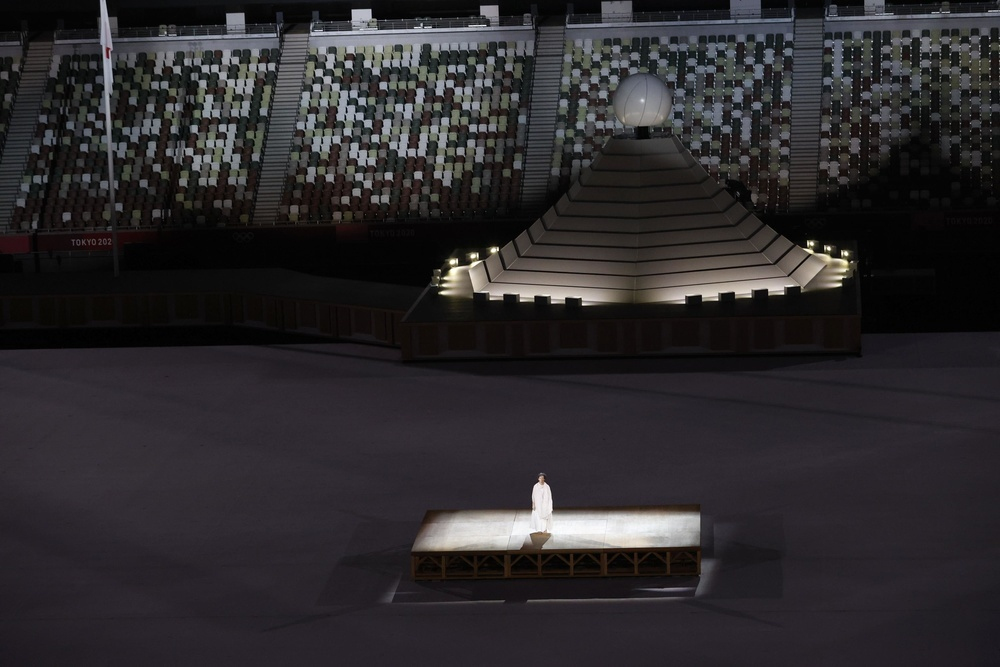 開会式で黙とうをささげる人(中央下)=23日夜、国立競技場