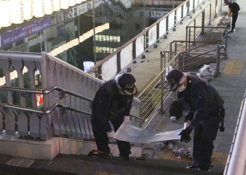 大阪・ミナミの道頓堀川そばの歩道を調べる府警の捜査員=2日午後11時11分