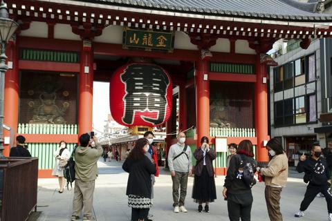東京・浅草の雷門前で写真撮影する人たち=25日午前