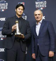 米大リーグのコミッショナー特別表彰を受けたエンゼルスの大谷翔平。右はマンフレッド・コミッショナー=26日、ヒューストン(共同)