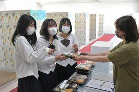 オンラインで注文し届けられた弁当を手に取る生徒たち=龍ケ崎市の県立竜ケ崎二高