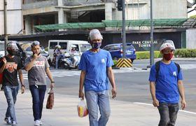 マニラ市街地でフェースシールドをずらして着用する人たち=6月(共同)