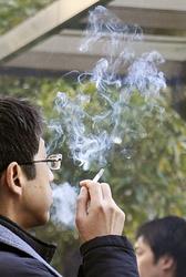 喫煙所でたばこを吸う男性
