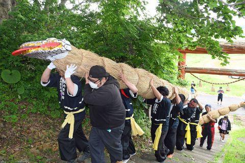全長約5メートルの「虫」を担ぎ、相内神明宮の階段を上る青年団員ら