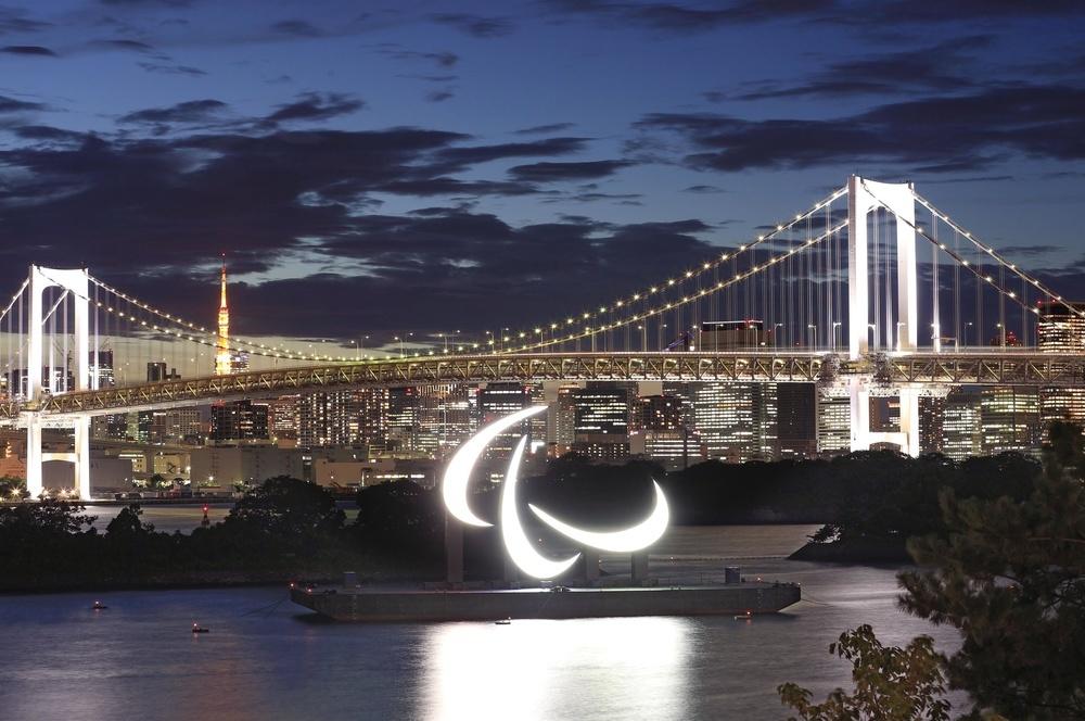 東京パラリンピックの開幕を控え、お台場に設置されたパラリンピックのシンボルマーク「スリーアギトス」。日が落ちると、穏やかな海に輝いた=20日午後7時5分