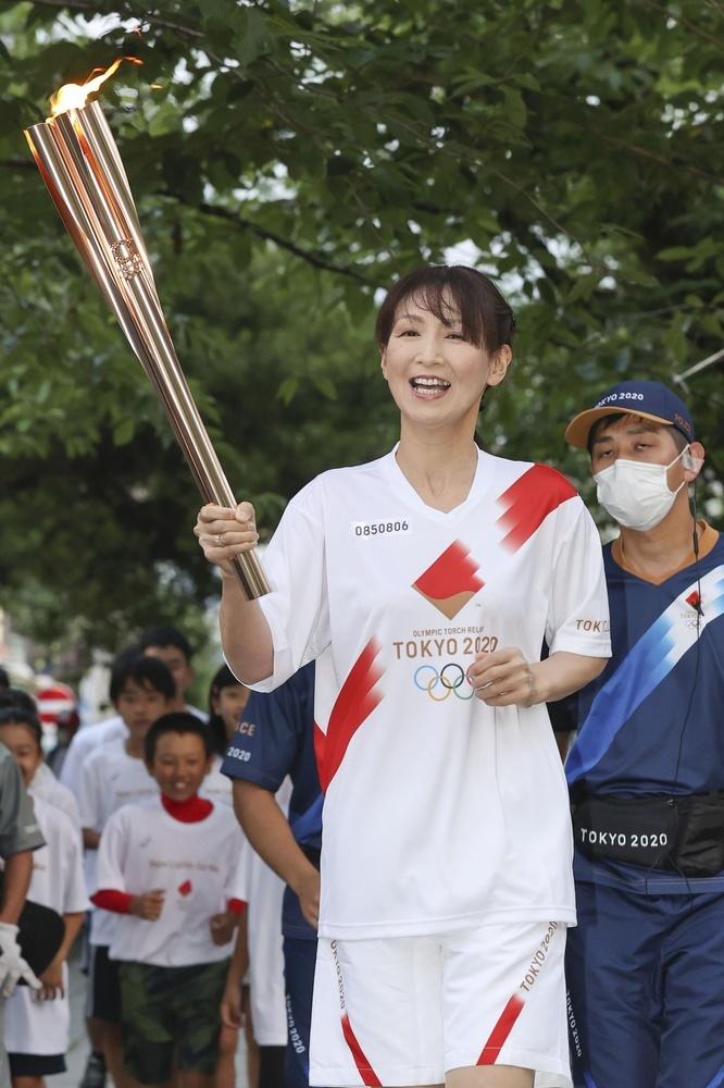 静岡新聞代表撮影、静岡県三島市を走る聖火ランナーの宮内千夏さん=24日午後