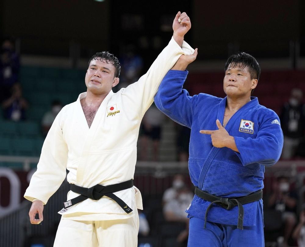 男子100㌔級決勝を終え、健闘をたたえ合うウルフ・アロン(左)と趙グハム=日本武道館