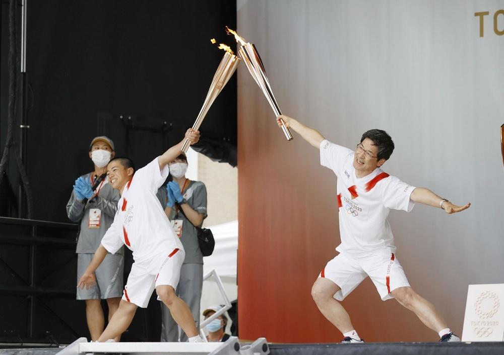 聖火リレーの代替イベントで、ポーズをとる池田嘉津弘さん(右)=3日午後、富山市