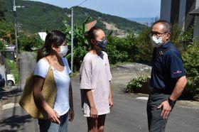 通学できなくなった内海小5年の鈴木麻音さん(中央)と話す村井博明校長(右)。後ろに約1キロ先の土砂崩れ現場の山肌が見えた=23日午後、宮崎市内海