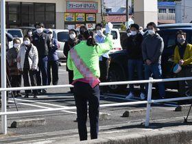 スーパーマーケットの前で買い物客らに向かい演説する候補者=23日午後、土岐市内