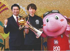優勝トロフィーを手にする(左から)田村社長、西村選手、マスコットキャラクター「ジャンボくん」=いずれも船橋市役所で