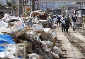 岡山県倉敷市真備町地区の道路に積み上げられたごみ=2018年7月