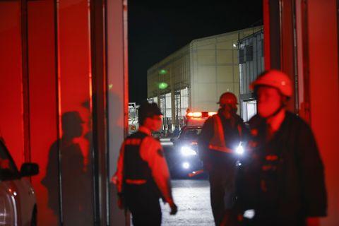 崩落事故のあったリニア中央新幹線の瀬戸トンネル工事現場付近に立つ警察官=27日午後10時38分、岐阜県中津川市