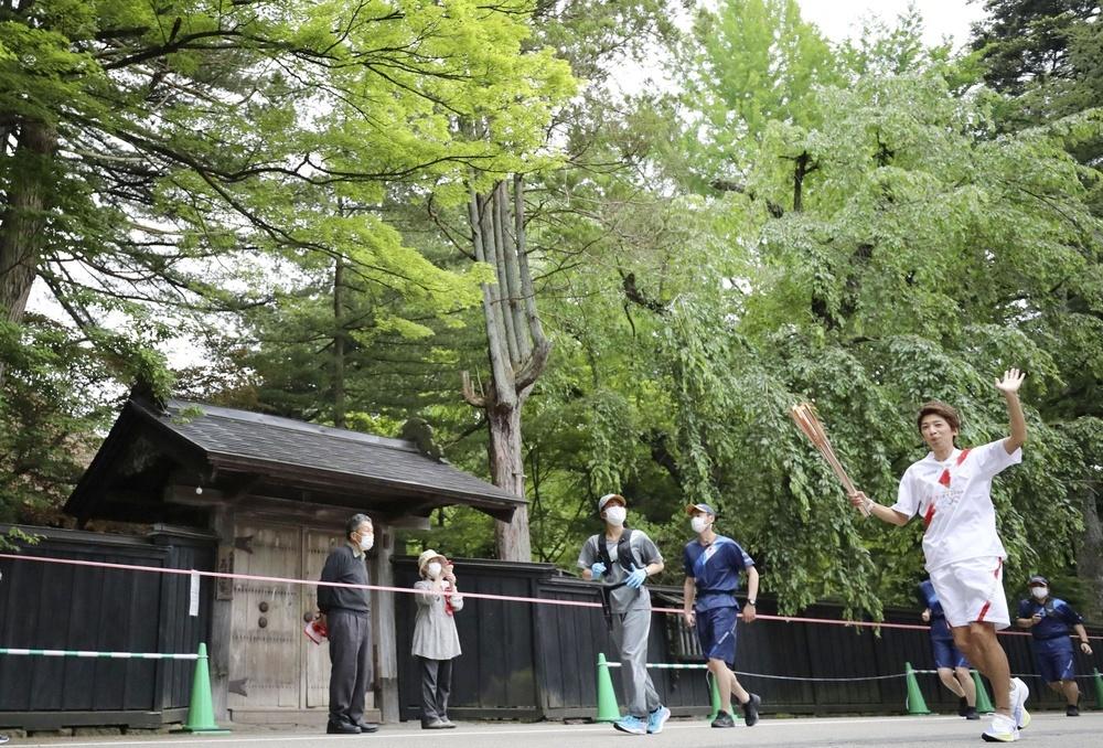 新緑に包まれた武家屋敷の前を、トーチを掲げて走る聖火ランナー=8日午後、秋田県仙北市