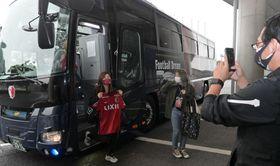 鹿島アントラーズのチームバスから降りる参加者たち=鹿嶋市神向寺の県立カシマサッカースタジアム