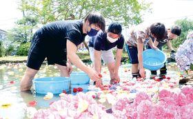「ニコニコ池」で水面に花を浮かべる諸井颯人さん(左から2人目)ら=11日午前、飯能市飯能