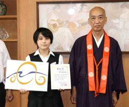 ロゴマークを手に写真に納まる黒木さん(左)と菅法主=香川県善通寺市文京町、善通寺一高