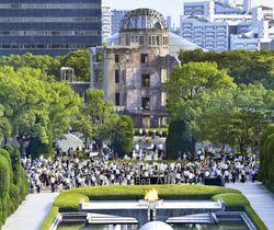 広島市の平和記念公園で黙とうする人たち。後方は原爆ドーム=6日午前8時15分