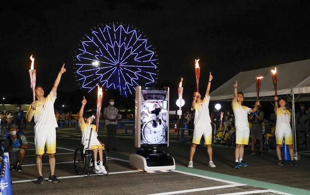 ロボットの画面に映し出された宇宙飛行士の星出彰彦さんとポーズをとる聖火ランナーら=21日夜、東京都江戸川区の葛西臨海公園