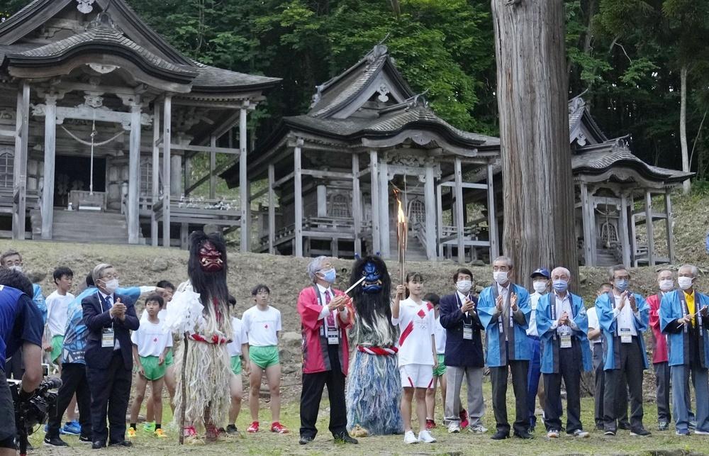 伝統行事「男鹿のナマハゲ」ゆかりの地、赤神神社五社堂で行われた聖火リレー。ランナーは佐藤杏さん(中央)=9日午後、秋田県男鹿市