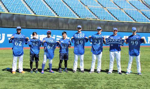 チームメートから贈られたユニホームやタオルを持って記念撮影に納まるエスコバー(左端)ら=横浜(球団提供)