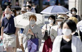 台風一過の晴天で気温が上がり、東京・銀座の交差点を日傘を差して歩くマスク姿の人たち=19日午後