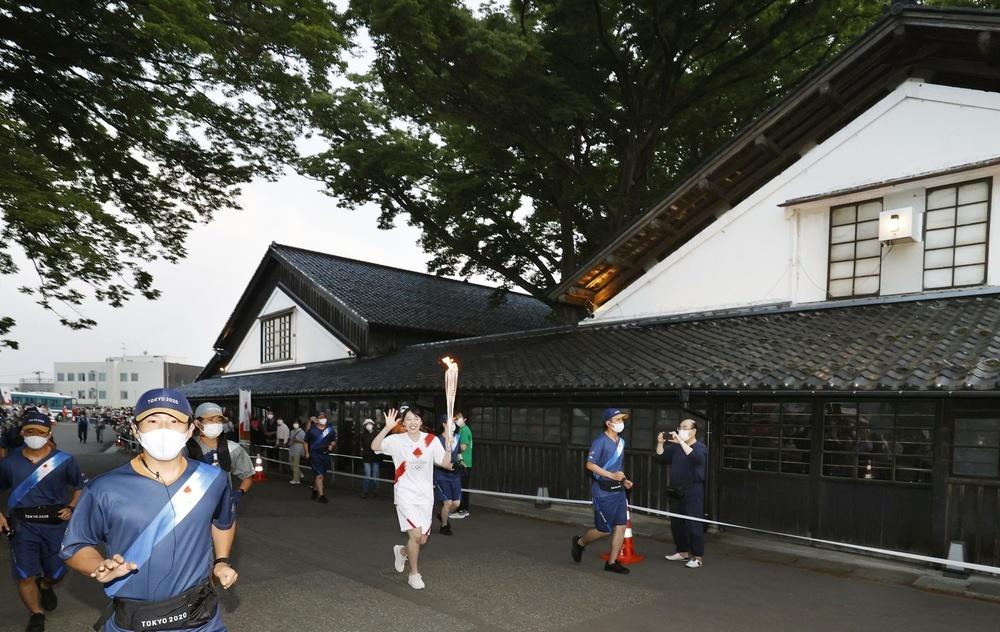 テレビドラマ「おしん」のロケ地「山居倉庫」を走る聖火ランナー=7日午後、山形県酒田市