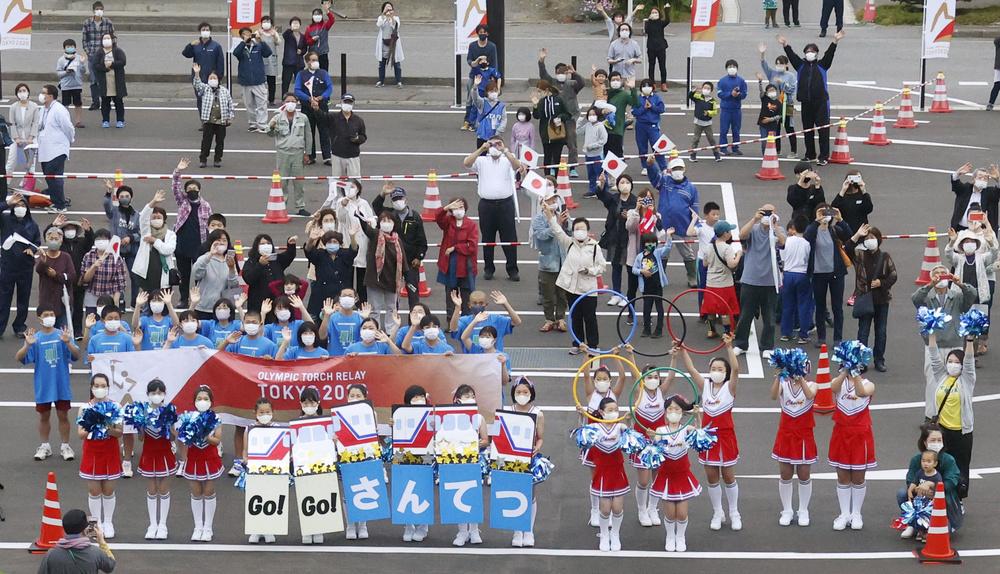 聖火を運ぶ三陸鉄道の列車に手を振る人たち=16日午後、岩手県普代村の普代駅前