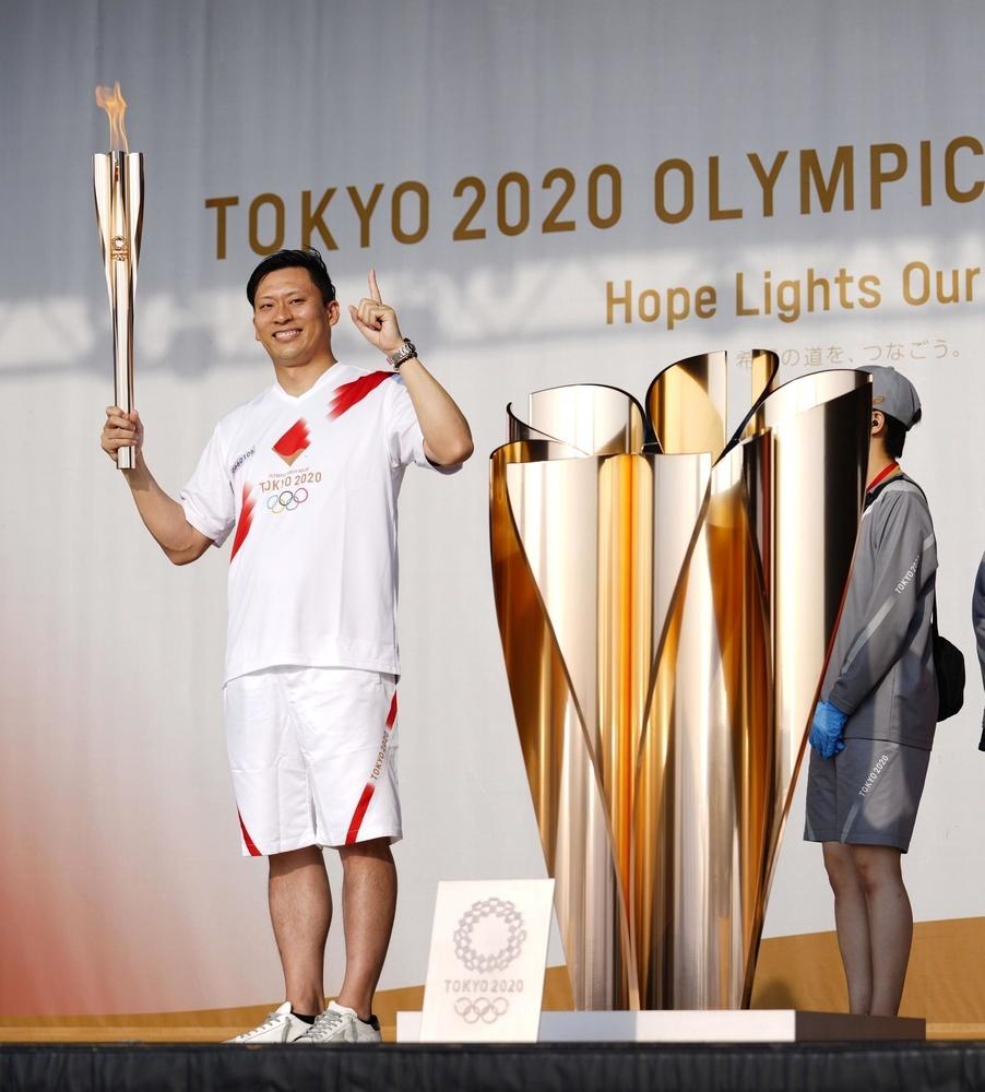 聖火リレーの代替イベントでトーチを掲げる荒瀬洋太さん=2日午後、富山県高岡市