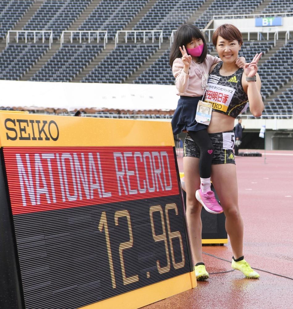 女子100㍍障害で12秒96の日本新をマークして優勝し、娘とポーズをとる寺田明日香=エディオンスタジアム広島、2021年4月29日撮影